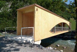 Puente sobre río con barandilla rellena de malla